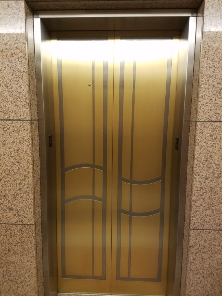 Satin finish bronze and stainless steel side by side, accenting the beautiful pattern in these elevator doors